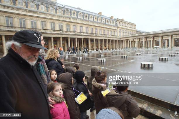 French sculptor Daniel Buren speaks to children in front of his halfdestroyed columns 15 January 2008 next to the historic stateowned PalaisRoyal...