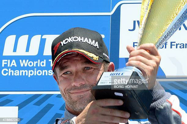 French Sebastien Loeb holds up his trophy as he celebrates on the podium after winning race 1 of the FIA World Touring Car Championship in Le...