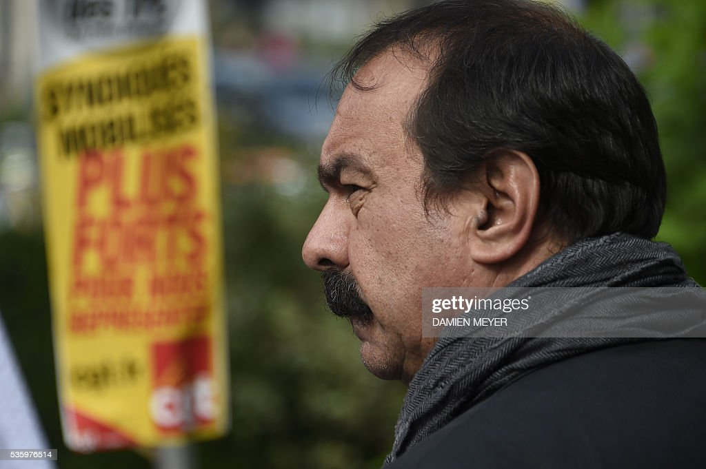 French secretary-general of the General Confederation of Labour (CGT) worker's union Philippe Martinez stands next to a CGT placard in Fougeres, western France on May 31, 2016, as he declared that the CGT filed a lawsuit for defamation against the head of France's bosses' federation. French employers' association Medef Pierre Gattaz accused unions of behaving like 'terrorists', as the fresh industrial unrest was set to hit transport just days before fans begin arriving for the start of the football championships on June 10. / AFP / DAMIEN