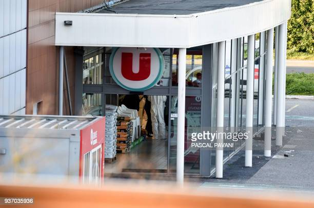 French security and forensic officers are seen inside the Super U supermarket in the town of Trebes southern France where a man took hostages killing...