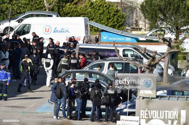 French security and police gather outside the Super U supermarket in the town of Trebes southern France where a man took hostages killing at least...