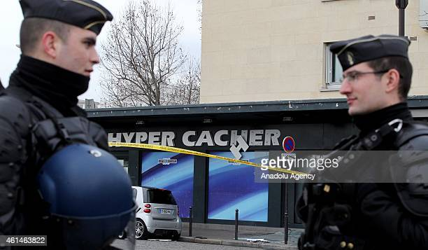 French security officials stand guard as people pay tribute to victims of the kosher supermarket in front of HyperCacher supermarket at Porte de...