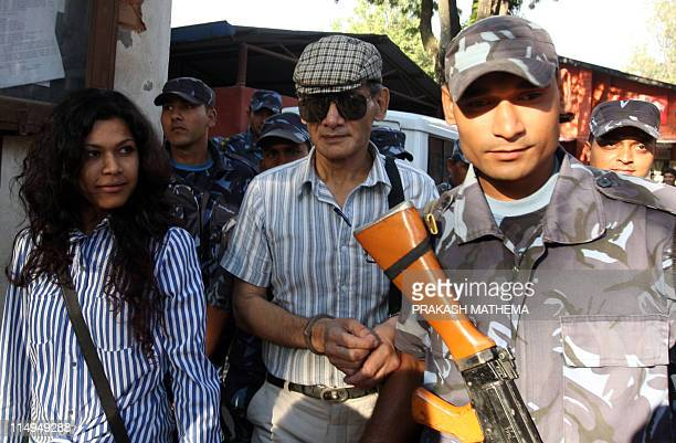 French serial killer Charles Sobhraj and Nihita Biswas who reportedly married Charles is guided by Nepalese policemen towards a waiting vehicle after...