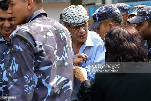 French serial killer Charles Sobhraj gestures while escorted by Nepalese police at a district court for a hearing on a case related to the murder of...