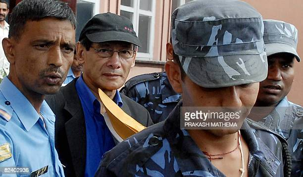 French serial killer Charles Sobhraj is guided by Nepalese policemen towards a waiting vehicle after a court ruling in Kathmandu on August 18, 2008....