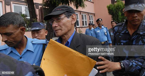 French serial killer Charles Sobhraj is guided by Nepalese policemen towards a waiting vehicle after a court hearing in Kathmandu on August 18, 2008....