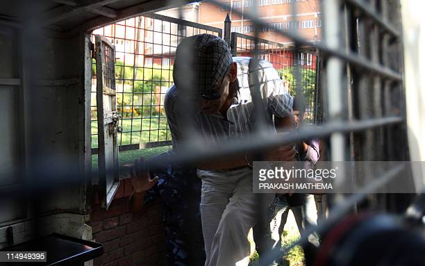 French serial killer Charles Sobhraj is helped into a police van after leaving a court hearing in Kathmandu on May 31, 2011. Charles Sobhraj, a...