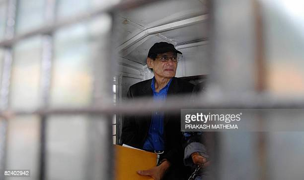 """French serial killer Charles Sobhraj sits in a waiting police van after a court hearing in Kathmandu on August 18, 2008. Known as the """"Bikini..."""