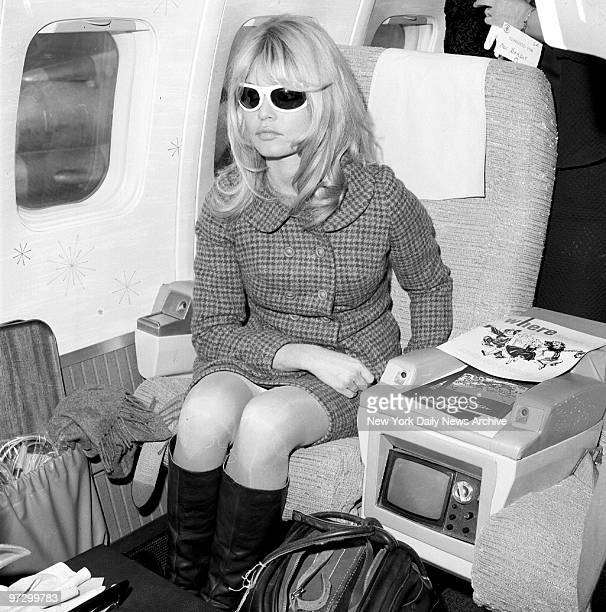 French sex kitten Brigitte Bardot wearing dark glasses to soothe her irritated winking eye sits in plane at Newark Airport before flying out to...