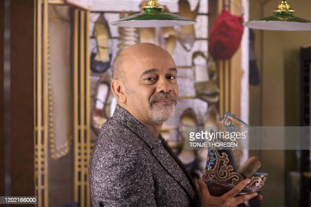French shoe designer Christian Louboutin poses with one of his creations during a photo session at the Palais de la Porte Doree in Paris a few days...