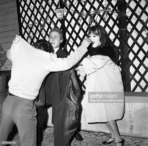 French showgirl Amanda Lear and Italian playboy Gianfranco Piacentini having a fight with a paparazzi coming out of La Piazzetta restaurant Rome 1959