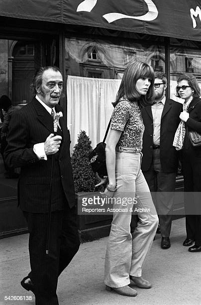 French showgirl Amanda Lear and Spanish painter Salvador Dali coming out of a restaurant 1960s