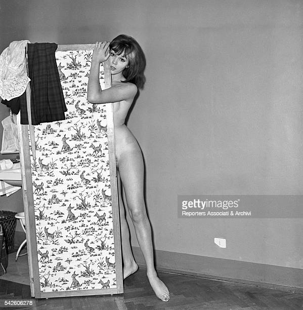 French showgirl Amanda Lear posing behind a screen in a hotel room for a sexy photoshooting 1959