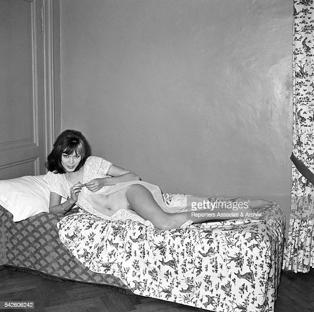 French showgirl Amanda Lear posing on a bed in a hotel room for a sexy photoshooting 1959