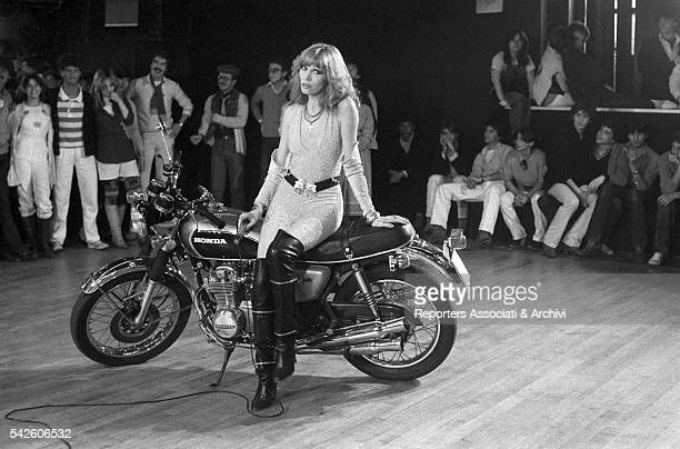 French showgirl Amanda Lear sitting on a motorbike while shooting the last scene in the movie Follie di notte directed by Joe D'Amato in a Roman club...
