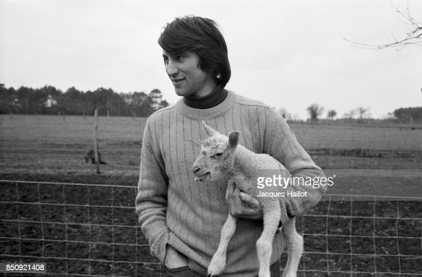 French singer Alain Barriere holding a lamb in a field