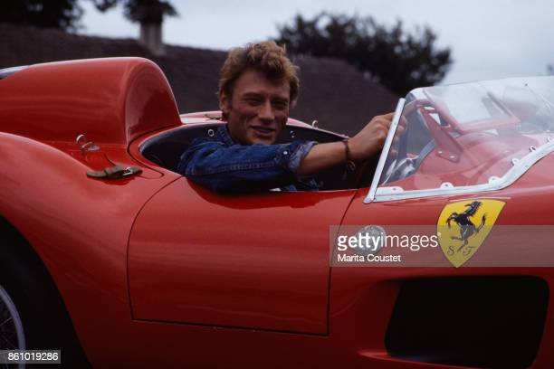 French singer and actor Johnny Hallyday driving a red convertible Ferrari 250 GT Testarossa