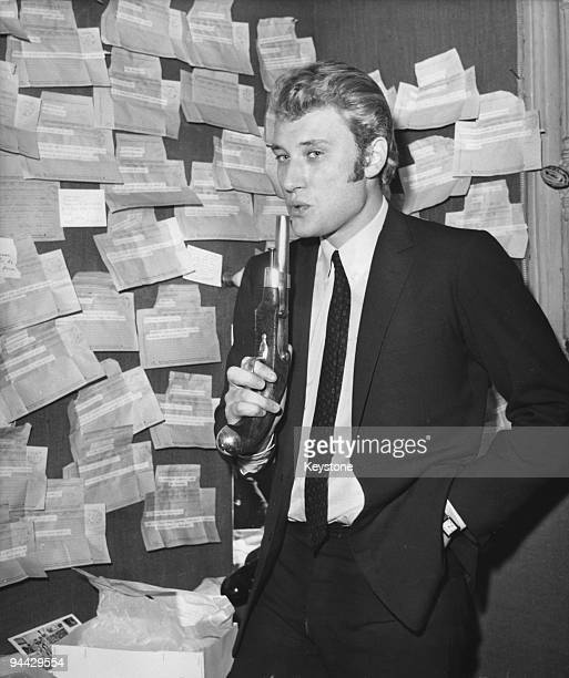 French singer and actor Johnny Hallyday in his dressing room at the Paris Olympia with a pistol and a number of telegrams sent by admirers 26th...