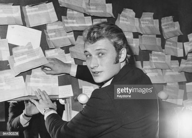 French singer and actor Johnny Hallyday in his dressing room at the Paris Olympia with a number of telegrams sent by admirers 26th November 1965