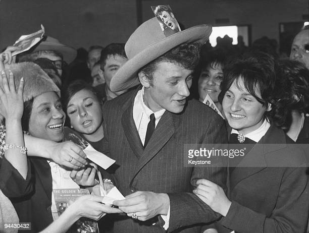 French singer and actor Johnny Hallyday surrounded by fans at Orly Airport in Paris upon his return from a tour of the United States 7th March 1962