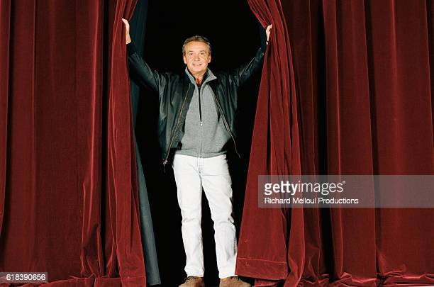 French singer and actor Michel Sardou opening the stage curtains at The Theatre of Paris