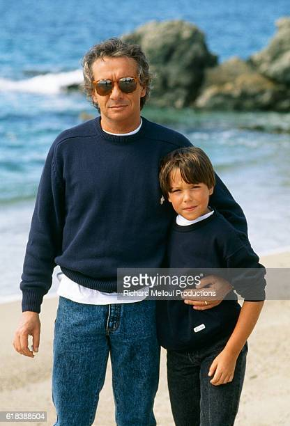 French singer and actor Michel Sardou relaxing with his son Romain on a beach in France