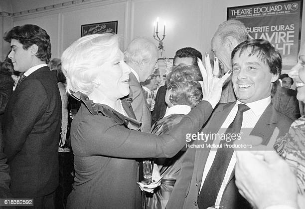 French singer and actress Line Renaud waves to comedian Thierry Le Luron at a party in Paris. The party was thrown to celebrate the 750th performance...