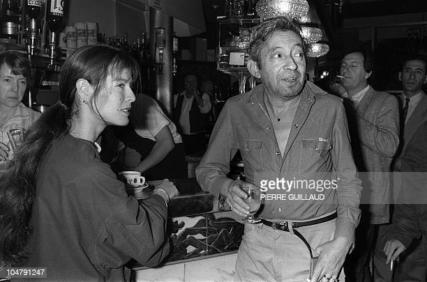 French singer and composer Serge Gainsbourg and his Eurasian companion Bambou have a drink on June 27 1985 in a cafe near the Casino of Paris where...