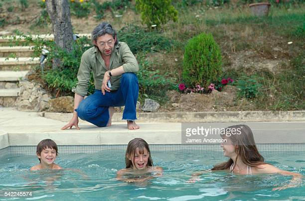 French singer and composer Serge Gainsbourg by the poolside watching his family in the swimming pool British singer and actress Jane Birkin her...