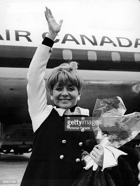 French singer Annie Cordy waves while holding a bouquet of flowers at Orly Airport Paris France April 4 1967 Cordy was en route to Montreal to sing...