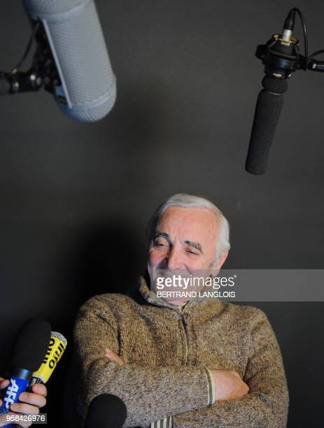 French singer Charles Aznavour addresses journalists after recording, with a dozen of French rappers and pop stars, a music video to raise funds for...