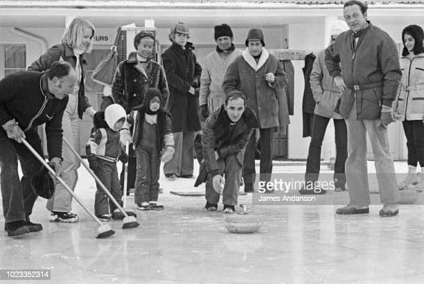 French singer Charles Aznavour playing curling with his wife Ulla Thorsell during their holiday in Switzerland with son Mischa and daughter Katia...
