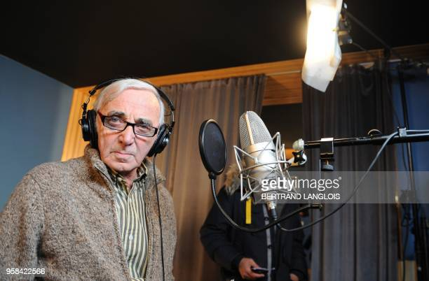 French singer Charles Aznavour poses while recording, with a dozen of French rappers and pop stars, a music video to raise funds for quake-stricken...