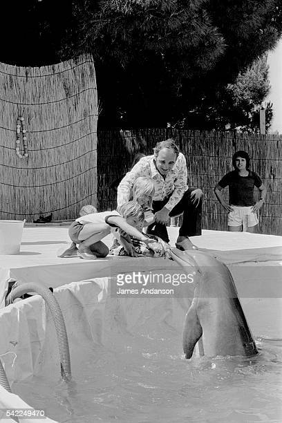 French singer Charles Aznavour with his children daughter Katia and son Misha playing with the dolphins at the water park in St Tropez