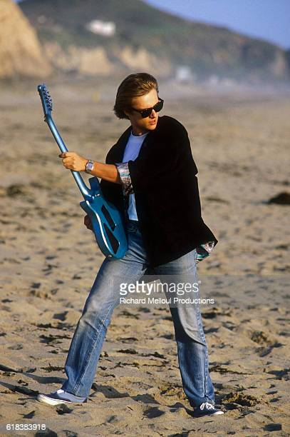 French singer David Hallyday plays his electric guitar on a sandy beach in Los Angeles.