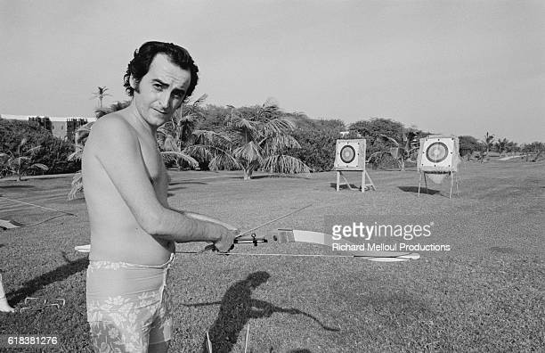French singer Dick Rivers spends time practicing his archery while vacationing in Dakar, Senegal.
