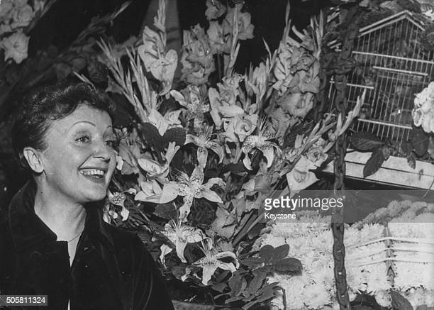French singer Edith Piaf admiring the many flowers recieved from friends as well a bird cage gift at a reception following her tour of America at...