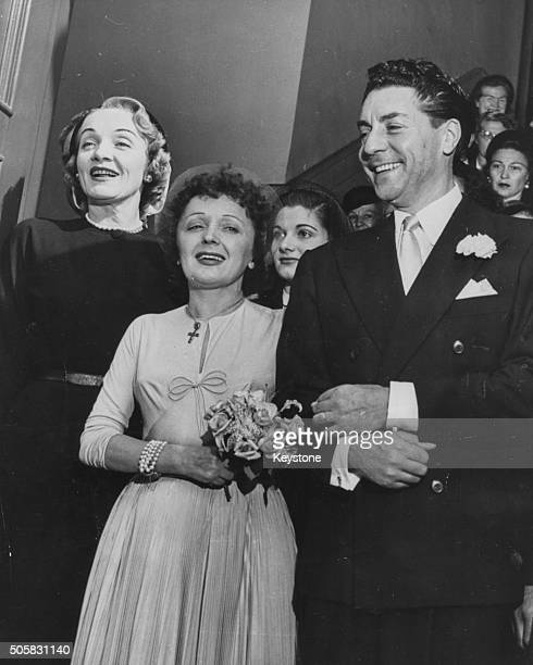French singer Edith Piaf arm in arm with her new husband Jacques Pills with Matron of Honor Marlene Dietrich on their wedding day in New York...