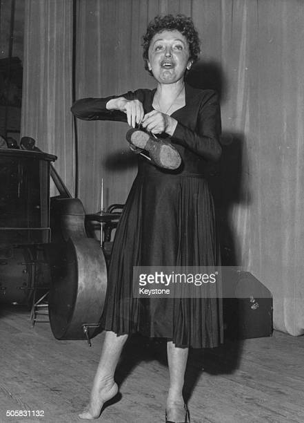 French singer Edith Piaf fixing one of her shoes as she prepares for a comeback concert following an illness at Melun Music Hall Paris circa 1959