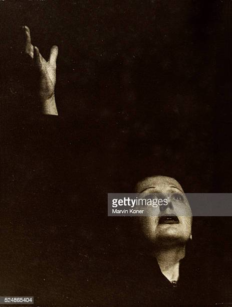 French singer Edith Piaf gestures with her right arm stretched upward circa 1960