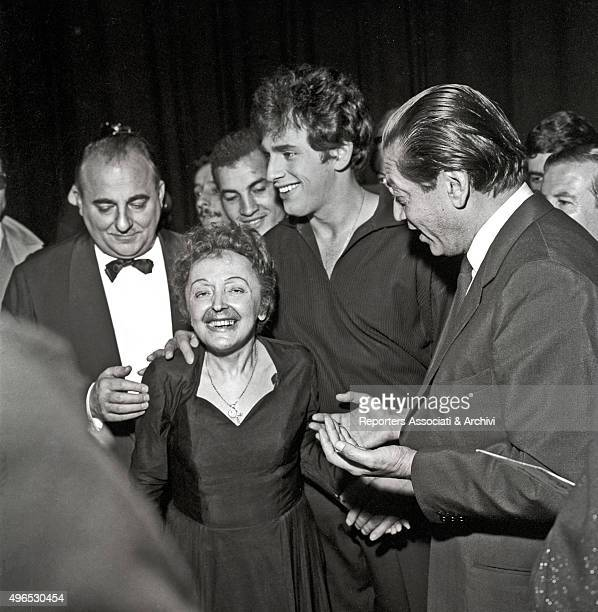 French singer Edith Piaf is surrounded by a crowd of fans after a concert at Olympia music hall At her left her young husband Greekborn French singer...