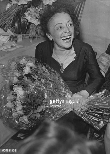 French singer Edith Piaf smiling and holding a bouquet of flowers after a concert circa 1959