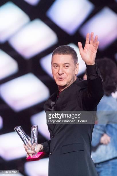 French singer Etienne Daho celebrates after receiving a special Honour Award during the 33rd 'Les Victoires De La Musique' at La Seine Musicale on...