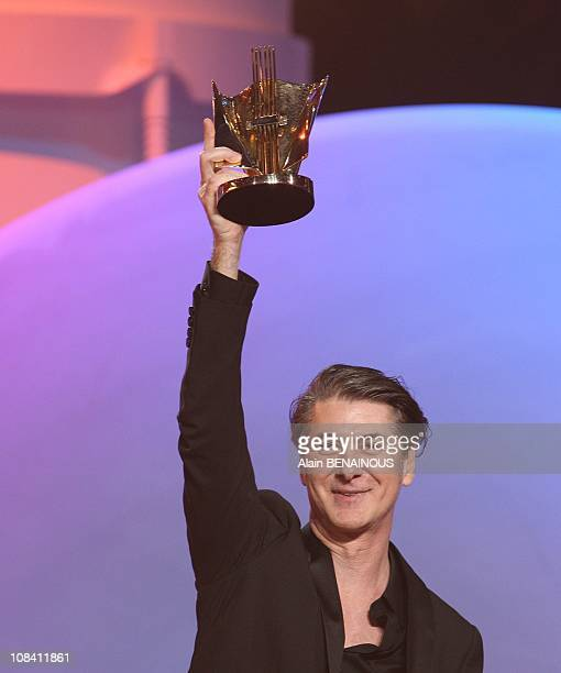French singer Etienne Daho is congratulated by French actress Anne Brochet after winning the best rock record of the year award during the 23rd...