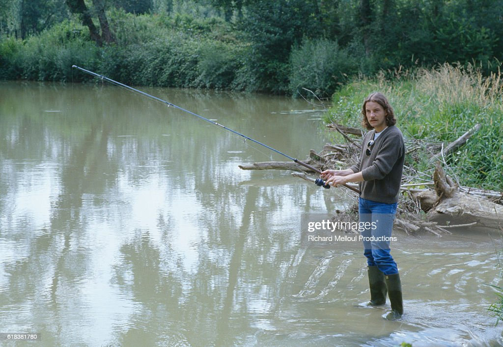 French Singer Francis Cabrel Fishing in a Lake : Photo d'actualité