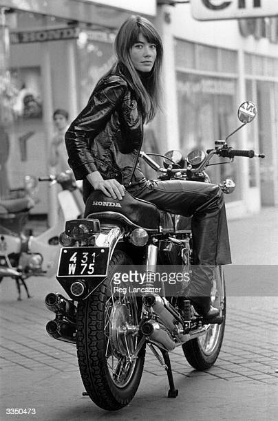 French singer, Francoise Hardy sitting on a motorbike.