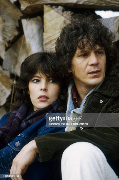 French singer Gerard Lenorman and his wife Caroline sit together near a stack of wood