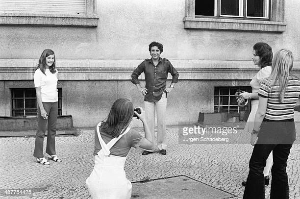 French singer Gilbert Bécaud being photographed by female fans during a visit to West Berlin Germany 1971