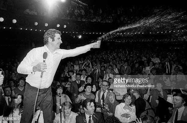 French singer Gilbert Becaud douses the audience with water during a performance on stage at the Olympia