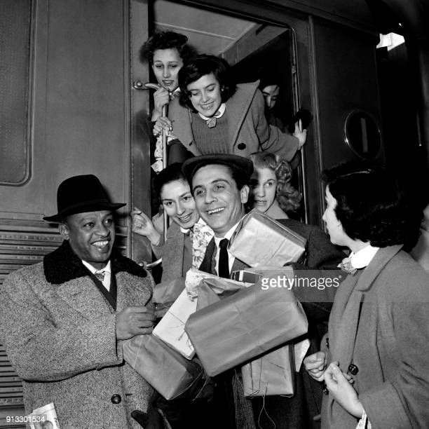 French singer Gilbert Becaud is welcomed by Jazz musician Lionel Hampton and fans for his arrival at the Paris Austerlitz station on February 4 1956...